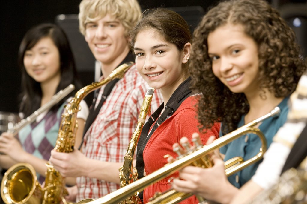 Four band students smiling at the camera