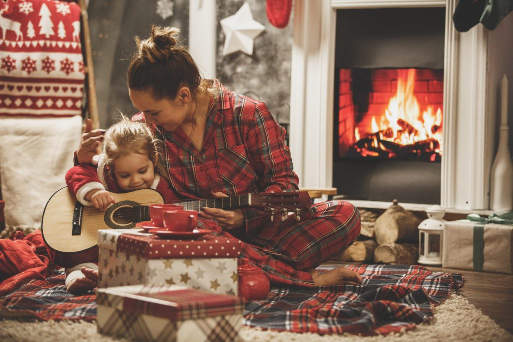 Young girl and mom playing with a guitar on Christmas