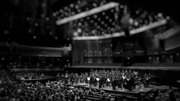 symphony orchestra in a concert hall preparing to perform before a large audience