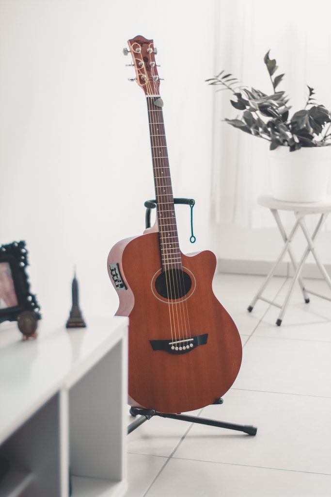 acoustic guitar on a guitar stand at home