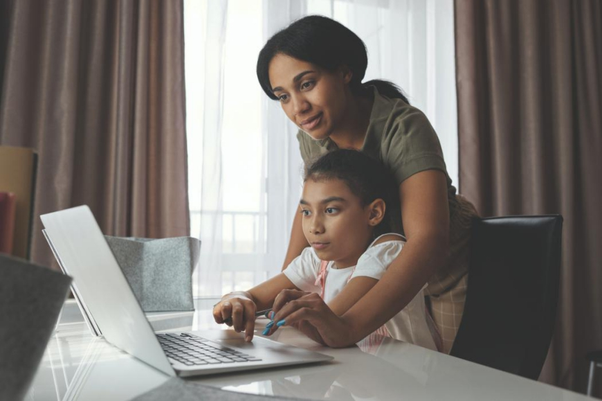 Mother and daughter looking at laptop together